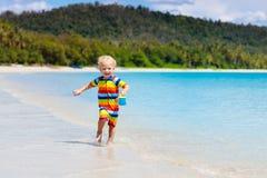 Jonge geitjesspel op tropisch strand Zand en waterstuk speelgoed stock afbeeldingen