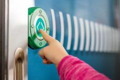 Jonge geitjesvinger die groene ronde aanrakingsknoop met pijlen duwen Transparante deur tussen vervoer in interlokale trein Moder stock foto's