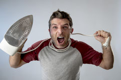 Jonge gekke wanhopige en gefrustreerde mens die het ijzer van de huishoudelijk werkholding doen Stock Foto's