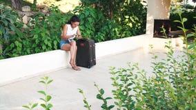 Jonge gelooide donkerbruine vrouw in borrels, zonnebril met een kofferzitting en gebruik smartphone in de zomer stock videobeelden