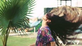 Jonge gelooide vrouw met lang haar onder tropische palmen in de zomer Langzame Motie stock videobeelden