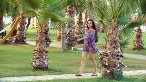 Jonge gelooide vrouw met lange haargangen langs weg tussen tropische palmen stock footage