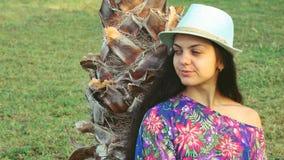 Jonge gelooide vrouw met lange haarzitting onder tropische palmen in de zomer stock videobeelden