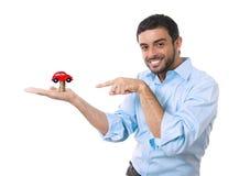 Jonge gelukkige aantrekkelijke mens met stuk speelgoed auto bovenop geïsoleerde muntstukkenstapel Stock Afbeeldingen
