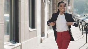 Jonge gelukkige Afrikaanse Amerikaanse onderneemster die in oortelefoons de stadsstraat lopen terwijl het luisteren aan de muziek stock footage