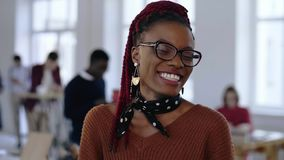Jonge gelukkige Afrikaanse creatieve ontwerper, professionele succesvolle bedrijfsvrouw in oogglazen die cheerfully op kantoor gl stock videobeelden