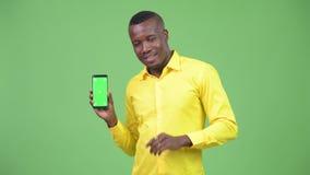 Jonge gelukkige Afrikaanse zakenmanvideo die en telefoon roepen tonen stock footage