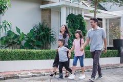 Jonge gelukkige Aziatische familie die samen lopen stock fotografie