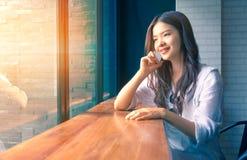 Jonge gelukkige Aziatische vrouw die haar telefoon met behulp van bij een koffie Royalty-vrije Stock Afbeeldingen