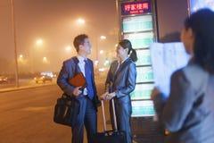Jonge gelukkige bedrijfsmensen die op een bus bij nacht wachten Stock Foto's