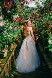 Jonge gelukkige bruidtribunes in gebloeide tuin royalty-vrije stock afbeeldingen