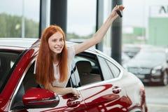 Jonge gelukkige die vrouw door een nieuwe auto bij autotoonzaal wordt verrast, gift van haar echtgenoot royalty-vrije stock afbeeldingen