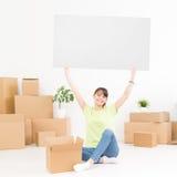 Jonge gelukkige die vrouw, een student, in een nieuwe flat wordt bewogen royalty-vrije stock afbeelding