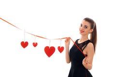 Jonge gelukkige donkerbruine dame met rood hart in studio glimlachen op camera geïsoleerd op witte achtergrond Rood nam toe Royalty-vrije Stock Afbeeldingen