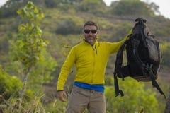 Jonge gelukkige en aantrekkelijke sportieve wandelaarmens die met trekkingsrugzak bij berg wandelen die vrije het genieten van re stock afbeeldingen
