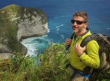 Jonge gelukkige en aantrekkelijke sportieve wandelaarmens die met trekkingsrugzak landschap van de wandelings het op zee klip vri royalty-vrije stock afbeelding