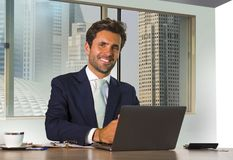 Jonge gelukkige en aantrekkelijke succesvolle zakenman die op modern kantoor in het centrale bedrijfsdistrict tevreden glimlachen royalty-vrije stock afbeeldingen