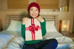 Jonge gelukkige en mooie Aziatische Amerikaanse vrouw in van de holdingskerstmis van de de winterhoed de huidige doos met lint op stock fotografie