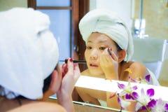 Jonge gelukkige en mooie Aziatische Koreaanse die vrouw thuis of hotelbadkamers in toilethanddoek wordt verpakt die vrolijke make royalty-vrije stock afbeelding
