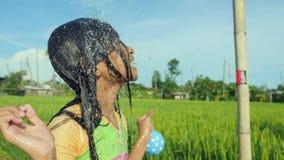 Jonge gelukkige en onbezorgd mooi kind 7 of 8 jaar oud in openlucht hebbend douche bij een mooi speels padieveld stock video