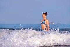 Jonge gelukkige en speelse rode haarvrouw in bikini die op overzeese het spelen met grote golven zwemmen die van het paradijs van royalty-vrije stock foto