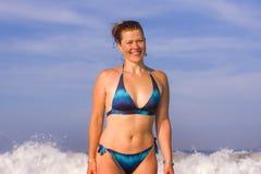 Jonge gelukkige en speelse rode haarvrouw in bikini die op overzeese het spelen met grote golven zwemmen die van het paradijs van royalty-vrije stock fotografie
