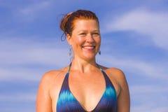 Jonge gelukkige en speelse rode haarvrouw in bikini die op overzeese het spelen met grote golven zwemmen die van het paradijs van stock foto