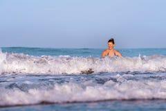 Jonge gelukkige en speelse rode haarvrouw in bikini die op overzeese het spelen met grote golven zwemmen die van het paradijs van stock foto's