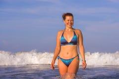 Jonge gelukkige en speelse rode haarvrouw in bikini die op overzeese het spelen met grote golven zwemmen die van het paradijs van stock fotografie