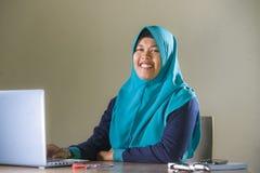 Jonge gelukkige en succesvolle Moslimstudentenvrouw in traditionele Islam hijab hoofdsjaal die aan bureau werken die met laptop b royalty-vrije stock foto's
