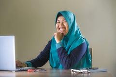 Jonge gelukkige en succesvolle Moslimstudentenvrouw in traditionele Islam hijab hoofdsjaal die aan bureau werken die met laptop b stock afbeelding