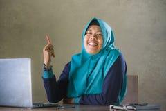 Jonge gelukkige en succesvolle Moslimstudentenvrouw in traditionele Islam hijab hoofdsjaal die aan bureau werken die met laptop b royalty-vrije stock foto