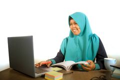 Jonge gelukkige en succesvolle Moslimstudentenvrouw in traditionele Islam hijab hoofdsjaal die aan bureau werken die met laptop b stock foto's