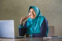 Jonge gelukkige en succesvolle Moslimstudentenvrouw in traditionele Islam hijab hoofdsjaal die aan bureau werken die met laptop b stock afbeeldingen