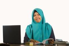 Jonge gelukkige en succesvolle Moslimstudentenvrouw in traditionele Islam hijab hoofdsjaal die aan bureau werken die met laptop b royalty-vrije stock afbeelding