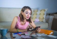 Jonge gelukkige en tevreden Latijnse vrouw die binnenlands financiënuitgaven en inkomen rekenschap geven die gebruikend calculato royalty-vrije stock foto