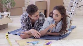 Jonge gelukkige familie die voor reparaties in de flat voorbereidingen treffen stock footage