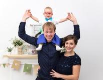 Jonge gelukkige familie met één éénjarigejongen op vaderschouders Stock Fotografie
