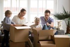 Jonge gelukkige familie met kinderen die dozen bij het bewegen van dag inpakken royalty-vrije stock afbeeldingen