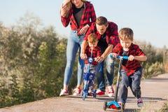 Jonge gelukkige familie met kinderen die pret in aard hebben De gelukkige autoped van de jonge geitjesrit in het park royalty-vrije stock afbeeldingen