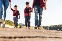 Jonge gelukkige familie met kinderen die pret in aard hebben Oudersgang met kinderen in het park stock afbeeldingen