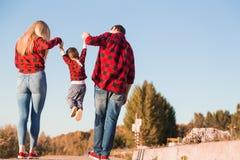 Jonge gelukkige familie met kinderen die pret in aard hebben Oudersgang met kinderen in het park stock fotografie