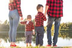 Jonge gelukkige familie met kinderen die pret in aard hebben Oudersgang met kinderen in het park royalty-vrije stock afbeelding