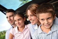 Jonge gelukkige familiezitting in autoboomstam royalty-vrije stock foto