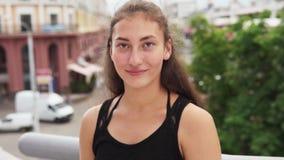 Jonge gelukkige gemengde rasvrouw die aan camera stedelijke straat bekijken stock video