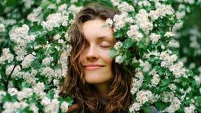 Jonge gelukkige glimlachende groen-eyed vrouw met bloemen Natuurlijke Schoonheid Royalty-vrije Stock Foto's