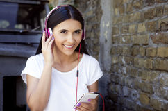 Jonge gelukkige glimlachende vrouw met hoofdtelefoons en telefoon Stock Afbeelding