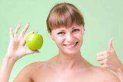 Jonge gelukkige glimlachende vrouw met omhoog appel en duimen Stock Foto's