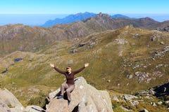 Jonge gelukkige het glimlachen vrouwenzitting op rand van de berg stock afbeelding