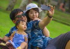 Jonge gelukkige houdende van Aziatische Koreaanse familie met ouders en zoete babydochter bij stadspark samen met vader die selfi stock foto